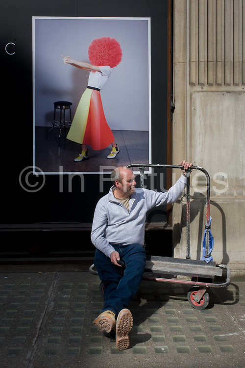 A removals man rests on a collection trolley beneath a Ilincic fashion model poster in a Mayfair street, London. <br /> Roksanda Ilincic—the British designer known for her colourful, feminine wares with a sculptural twist—revealed today that, early next year, she'll bow her first store at 9 Mount Street. Having studied Architecture and Applied Arts at university in Belgrade, her designs are soon to fill finished windows in Mayfair, central London.