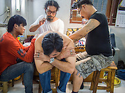 "14 MARCH 2014 - NAKHON CHAI SI, NAKHON PATHOM, THAILAND:  An archan gives a man a sak yant tattoo at Wat Bang Phra. Wat Bang Phra is the best known ""Sak Yant"" tattoo temple in Thailand. It's located in Nakhon Pathom province, about 40 miles from Bangkok. The tattoos are given with hollow stainless steel needles and are thought to possess magical powers of protection. The tattoos, which are given by Buddhist monks, are popular with soldiers, policeman and gangsters, people who generally live in harm's way. The tattoo must be activated to remain powerful and the annual Wai Khru Ceremony (tattoo festival) at the temple draws thousands of devotees who come to the temple to activate or renew the tattoos. People go into trance like states and then assume the personality of their tattoo, so people with tiger tattoos assume the personality of a tiger, people with monkey tattoos take on the personality of a monkey and so on. In recent years the tattoo festival has become popular with tourists who make the trip to Nakorn Pathom province to see a side of ""exotic"" Thailand.  PHOTO BY JACK KURTZ"