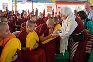 Western woman contratulating some of the twenty nuns to be awarded Geshe-ma degrees sitting in the front row in the courtyard of Drepung Lachi Monastery in Mundgod, Karnataka, India on December 22, 2016