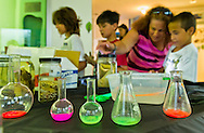 Seaford, New York, U.S. 20th July 2013. L-R, TRINITY GARCIA, 9, his mom DONNA GARCIA, of Lindenhurst, and BRIAN CIUFFO, 7, and MICHAEL CIUFFO, 10, of North Massapequa, are at the Slime Making science project table at Science Exploration Moon Day, presented by Long Island Fringe Festival 5, at the Tackapuahsa Museum and Preserve, the host of this family event. The beakers are filled with colorful glow-in-the-dark liquid from glow sticks.