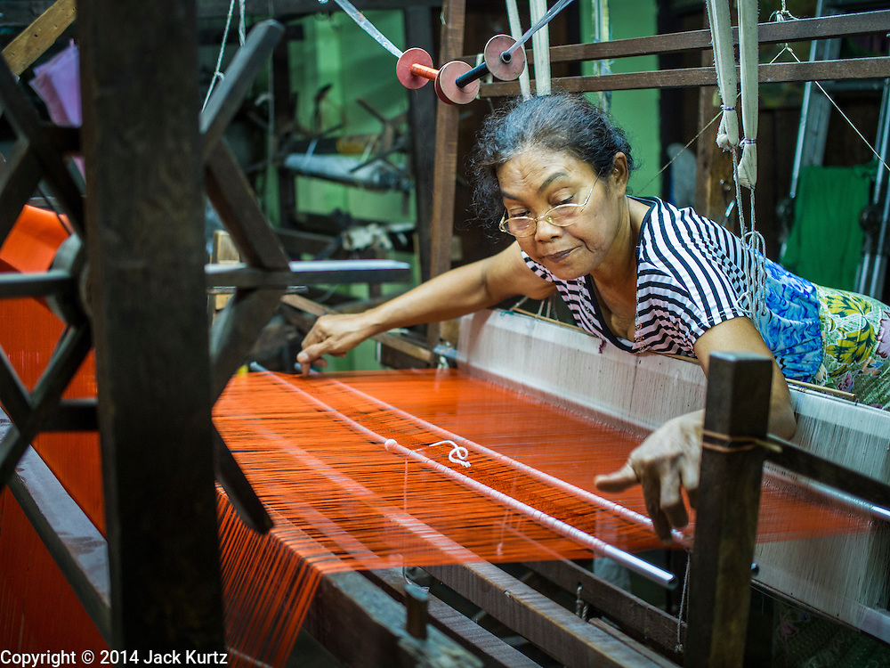 22 OCTOBER 2014 - BANGKOK, THAILAND:  A woman works in a silk weaving workshop in the Ban Krua neighborhood of Bangkok. The neighborhood was originally settled by Cambodian Chams who came to Thailand (Siam) at the invitation of the Thai (Siamese) King after they sided with Siam against the Khmer monarchy during a Siam/Khmer war in the 19th century. Most of the Chams were silk weavers.       PHOTO BY JACK KURTZ