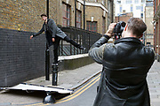 A photographer shoots a model as he balances on a bollard during a fashion shoot in the streets of Shoreditch, London, UK Shoreditch, an area that was dominated by light industry is now home to creatives and the streets are often used as a backdrop for fashion shoots.
