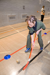 Young boy playing a game of indoor hockey in the sports hall of his local leisure centre,