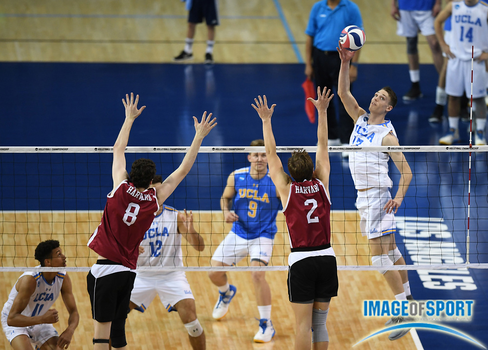 UCLA Bruins opposite hitter Christian Hessenauer (17) spikes the ball as Harvard Crimson middle blocker Trevor Dow (8) and setter Marko Kostich (2) defend during the opening round game of the NCAA college volleyball championship in Los Angeles, Tuesday, May 1, 2018. UCLA defeated Harvard 23-25, 25-21, 25-11, 25-21.