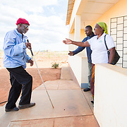 CAPTION: Though Caisse developed the core skills necessary to manage his business in spite of his disability, writing remained a challenge for him. It was for this reason that he took up Braille lessons through ACAMO. Arriving for his class, Caisse is seen here being greeted by two staff members. He is able to reach class by himself with the aid of his white cane, which has substantially increased his mobility. The cane has three main functions: to guide users as they walk; to help others identify users as visually impaired; and to help users develop confidence in their ability to get around, giving them a greater sense of freedom and independence. LOCATION: Lulimile Village, Lichinga, Niassa Province, Mozambique. INDIVIDUAL(S) PHOTOGRAPHED: From left to right: Casimiro Adua Caisse, unknown and Anissa Bernado Binamur.