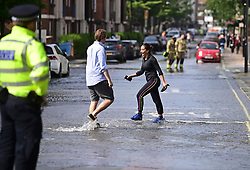 © Licensed to London News Pictures. 24/06/2021. London, UK. Members of the public wade through water in St John's Wood, North London, where a burst pipe has has cause flooding across a number of streets in the area. Photo credit: Ben Cawthra/LNP