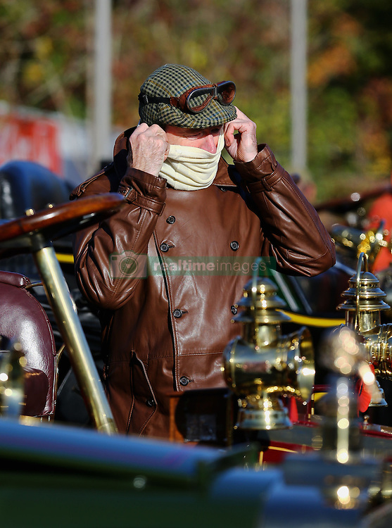A driver in the Bonhams London to Brighton Veteran Car Run prepares to depart following a stop in Crawley, Sussex.