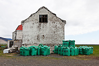 Old farm house in South Iceland. Large green sacks of fertilizer in front of the building.