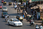 Mercedes S Class luxury saloon and auto rickshaws among traffic in Bandra near BKC Complex in Mumbai, India