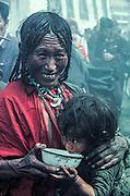 Mother feeds child during kora (circuit) of Jokhang temple, Lhasa, Tibet
