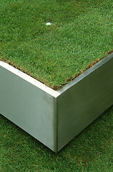Detail of giant stainless steel tray filed with soil and turfed. Design Diarmuid Gavin