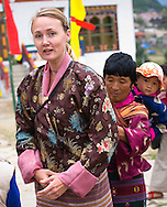 Local helping a traveler with her traditional dress at the Haa Tsechu (festival), Haa Valley, Bhutan