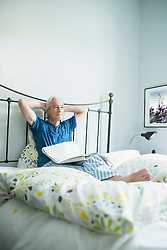 Mature man sitting with newspaper in bed, looking away