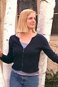 Beautiful blond woman age 30 standing in the birch trees.  St Paul Minnesota USA