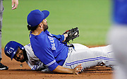 Kansas City Royals' Jorge Bonifacio, left, smiles after he and Toronto Blue Jays second baseman Devon Travis, right, fall to the ground after he was tagged out attempting to double on a hit to left field in the second inning of a baseball game at Kauffman Stadium in Kansas City, Mo., Thursday, Aug. 16, 2018. (AP Photo/Colin E. Braley)
