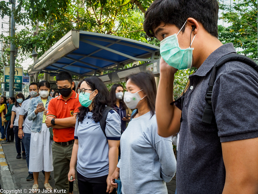 31 JANUARY 2019 - BANGKOK, THAILAND:   People wearing breathing masks because of the high pollution levels in Bangkok wait in line for motorcycle taxis at a Bangkok subway stop. The Thai government has closed more than 400 schools for the rest of the week because of high levels of pollution in Bangkok. At one point Wednesday, Bangkok had the third highest level of air pollution in the world, only Delhi, India and Lahore, Pakistan were worst. The Thai government has suspended some government construction projects and ordered other projects to take dust abatement measures. Bangkok authorities have also sprayed water into the air in especially polluted intersections to control dust. Bangkok's AQI (Air Quality Index) Thursday morning was 180, which is considered unhealthy for all people.      PHOTO BY JACK KURTZ