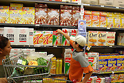 (MODEL RELEASED IMAGE). While the Brown family of Riverview, Australia are used to living with a nearly-empty refrigerator, they look forward to the days when it's full?every two weeks a new check appears and the family goes to the supermarket. Here, Vanessa looks on as John goes to get a box of cereal.(Supporting image from the project Hungry Planet: What the World Eats.)