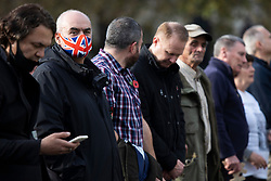 © Licensed to London News Pictures. 08/11/2020. London, UK. A man wears a union flag mask as he waits to take part in a minute's silence as part of Remembrance Sunday .  Photo credit: George Cracknell Wright/LNP