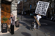Seen from the rear, a Christian religious message stating that without Jesus Christ, we will burn in the lake of fire, is held by a young man who walks past a woman placing a Covid mask on her face, on 12th October 2021, in London, England.