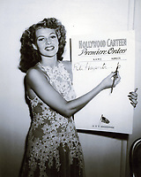 1944 Rita Hayworth signing up people for the premiere of the movie Hollywood Canteen.