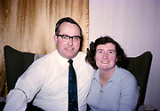 Husband and wife head and shoulders portrait sitting together at home, British culture 1967