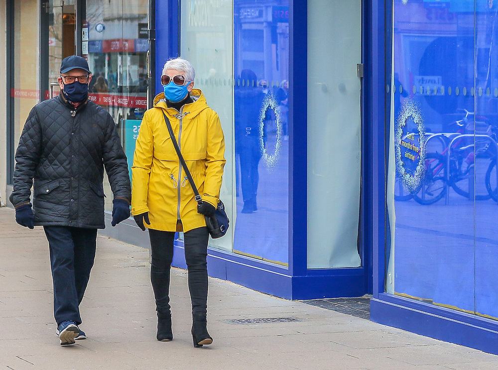 1st March, Cheltenham, England. A man and woman walk past a shut o2 during the third national lockdown.
