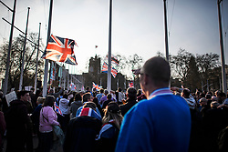 © Licensed to London News Pictures. 29/03/2019. London, UK. The Union Flag flies over the heads of Brexit supporters as they gather outside the Houses of Parliament after MPs rejected Theresa May's withdrawal agreement. Photo credit: Ben Cawthra/LNP