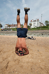 (c) Licensed to London News Pictures. 05/05/2014. Essex, UK. May Day Bank Holiday at traditional resort, Southend on Sea. Iranian, Afshin, prefers to work out with some stretches on the beach. Photo credit Simon Ford/LNP