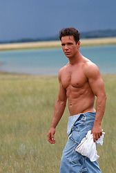 Muscular shirtless man walking in a field in New Mexico