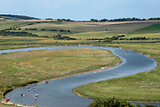 Paddle boarders on the winding estuary of the Cuckmere river as it passes through the South Downs National Park next to Seven Sisters on the 25th of August 2021 near Seaford, East Sussex, United Kingdom. Kayaking and Paddle boarding have become very popular in the UK, these are rented out to the public by a company called Buzz Active based on the banks of the Cuckmere River.
