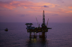 Stock photo of an offshore drilling rig at sunset