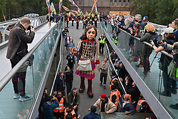 © Licensed to London News Pictures. 23/10/2021. London, UK. Little Amal, the 3. 5 metre tall puppet of a nine year old migrant Syrian girl crosses the Millenium Bridge. The giant puppet has nearly completed a 5,000 mile journey across Europe, aiming to bring attention needs of young refugees and the journeys for a better life. Photo credit: Ray Tang/LNP