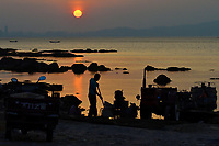 """A fisherman cleaning his aquaculture equipment at dusk, Yangma island, prefecture Yantai, Shandong, China. Yangma Island is situated by the Yellow Sea and it is called """"the pearl in the sea"""".Yangma island, prefecture Yantai, Shandong, China. Yangma Island is situated by the Yellow Sea and it is called """"the pearl in the sea""""."""