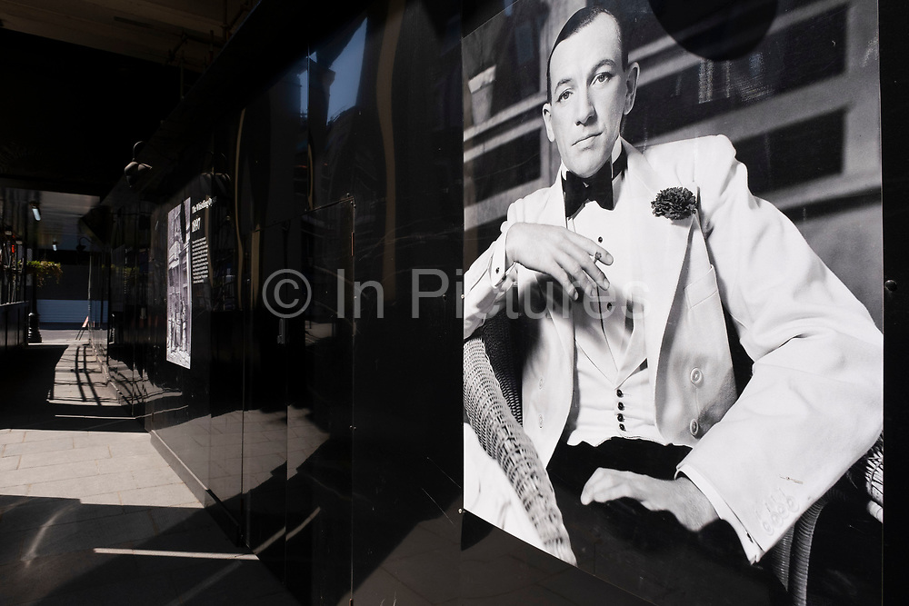 Famous old black and white photograph of Noel Coward used on a hoarding outside a theatre under redevelopment in the West End on 25th June 2020 in London, United Kingdom. Sir Noel Coward was an English playwright, composer, director, actor and singer, known for his wit, flamboyance.