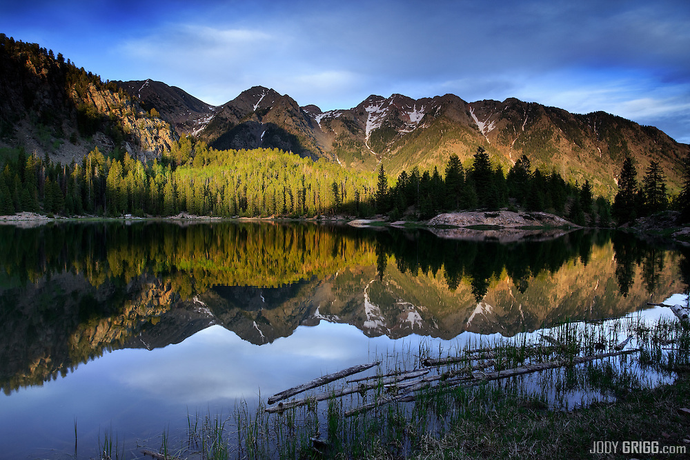 Twiligt Peaks reflect in a very still Potato Lake at sunset near Coal Bank Pass north of Durango, Colorado.