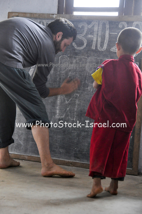 Teacher and young novice monks near the blackboard at a school in Sikkim, India