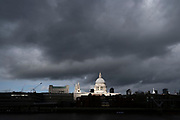 The skies darken above the sunlit dome of St Paul's Cathedral and the City of London on 26th October 2020, in London, England.