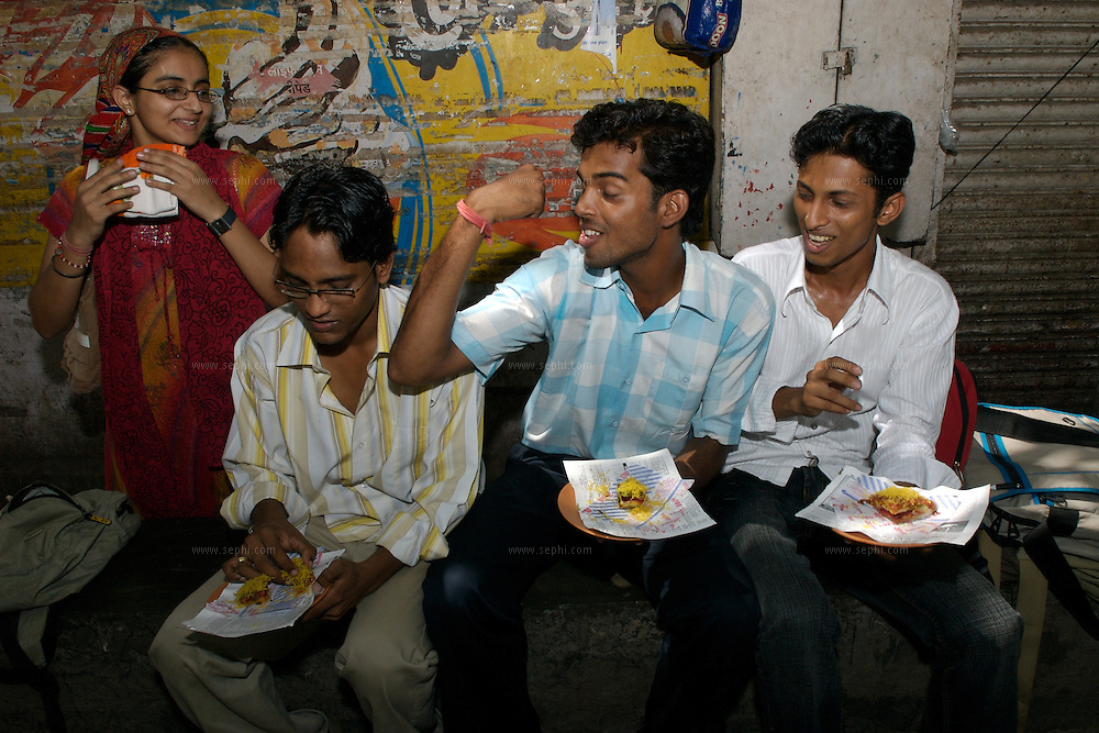 Students from a near-by college enjoy the famous Mumbai Veg Sandwich at Khao gali, the food street, Mumbai, June 2007