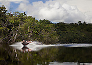 A dugout canoe carrying tourists speeds along the Canaima River towards Angel Falls, in Canaima National Park, Venezuela