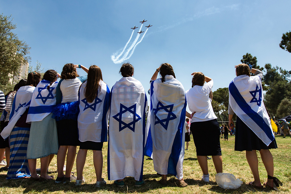 People draped in Israel's national flags watch as Israeli Air Force Aerobatic Team fly over Sacher Park in Jerusalem during Israel's 67th Independence Day, on May 12, 2016. Israel is celebrating its annual Independence Day, marking 68 years since the creation of the Jewish state.