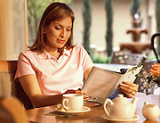 A woman reads a book while drinking her morning coffee at a resort