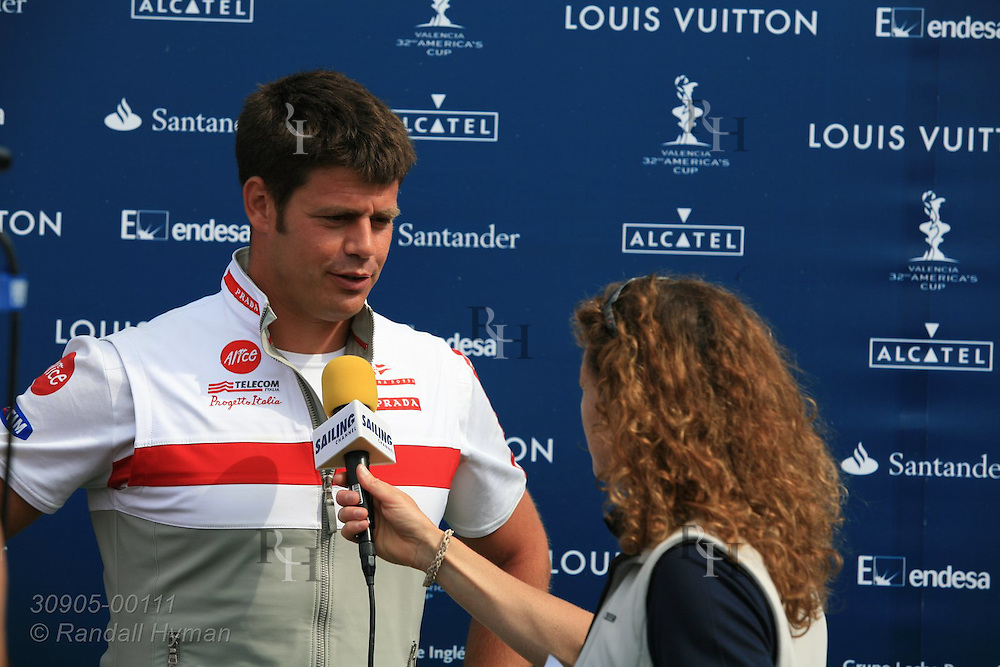 Crewman from Italy's Luna Rossa Challenge team talks to reporter after day of fleet racing at 32nd America's Cup competition; Valencia, Spain.