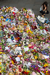 A woman views floral tributes to the victims of the terrorist attack on London Bridge and Borough Market one week after the incident.