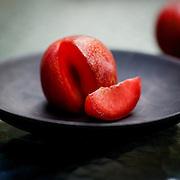 Red Juicy Plums on Black Plate