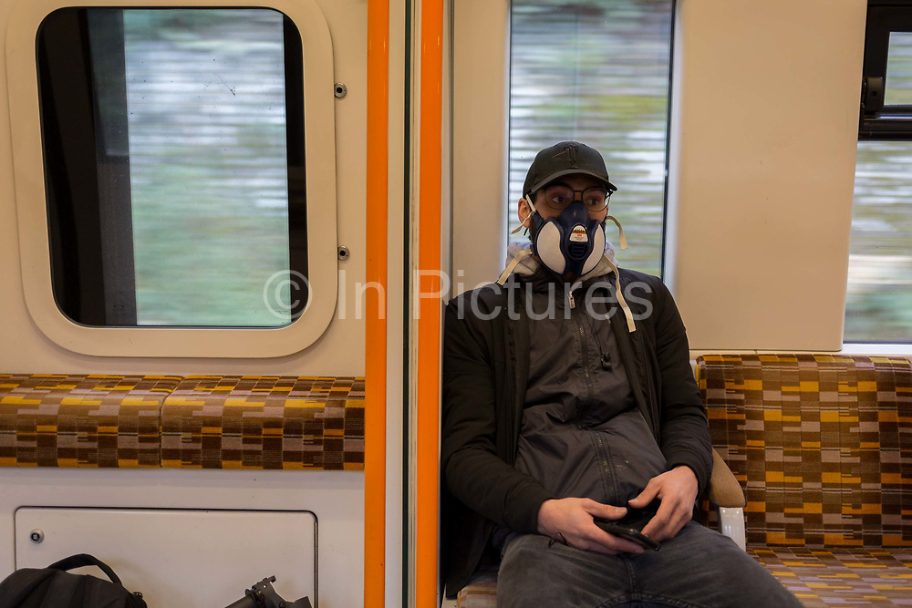 As the UK government announces further Coronavirus-related restrictions to its citizens, with the immediate closure of pubs, cafes, gyms and cinemas, and the worldwide number of deaths reaching 10,000 with 240,000 cases, 953 of those in London alone, a male rail passenger wears an industrial maintenance free face mask made by 3M, a variety that gives Effective and comfortable protection against organic vapour and hazardous particulates, on an Overground train travelling across south London, on 20th March 2020, in London, England.