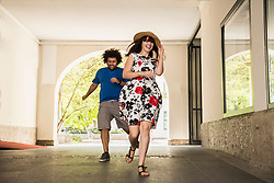 Happy young couple running in building corridor