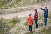 People are seen walking across Bamburgh coastal sand dunes on Wednesday, March 17, 2021. The dunes are an area of over 40 hectares situated around the village of Bamburgh in Northumberland, England by the North sea. (Photo/ Vudi Xhymshiti)