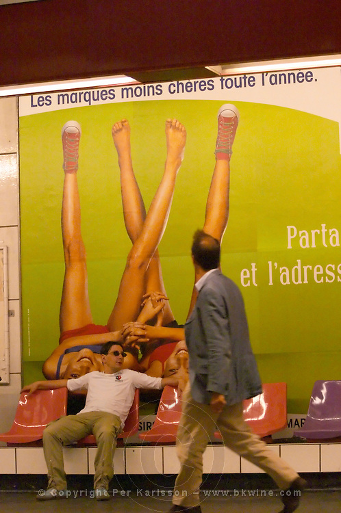 A man in sunglasses sitting on a bench in the Paris metro in front of a publicity poster. The poster has the text the least expensive brands all year round and the picture shows two young pretty women lying on their back with their legs stretched upwards and spread apart each woman only wearing one shoe and holding hands. Another man walking past looking up at the legs and thighs of the girls. Paris, France, Europe