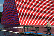 Artist Christo walks out onto a pontoon to view his art installation 'The Mastaba', by artist Christo, installed on the Serpentine lake in Hyde Park on June 18th 2018 in London, United Kingdom. The sculpture consists of 7,506 stacked barrels, painted in shades of red, white, blue and mauve. The completed piece forms part of an exhibition by Christo and his late wife, Jeanne-Claude's work, entitled Christo and Jeanne-Claude: Barrels and The Mastaba 19582018 to be held at The Serpentine Gallery.