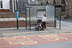 Mother waiting at bus stop with baby